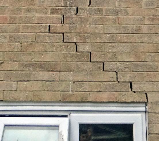 crack in brick wall above door